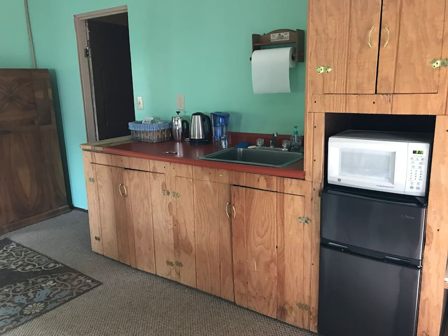 Kitchen area with sink, microwave, fridge