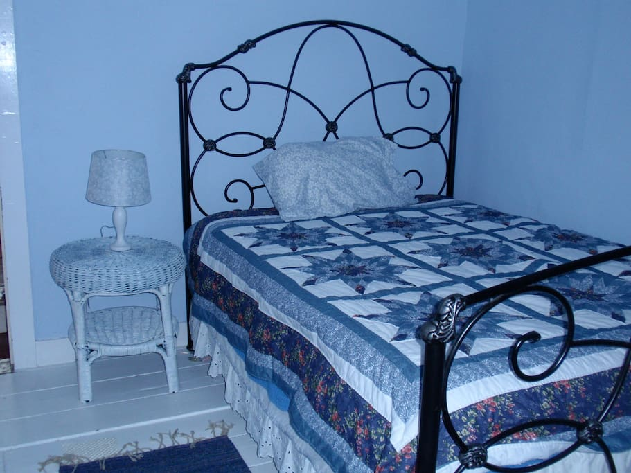 Large bedroom with full foam mattress and simple antique furnishings