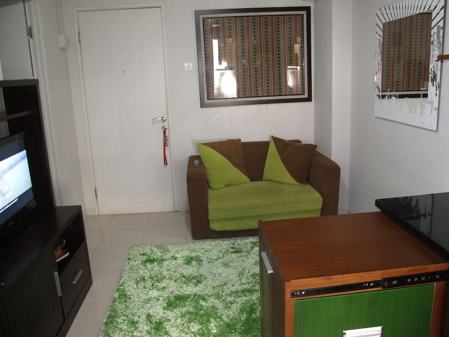 living room with sofa bed, carpet, TV cable, DVD and water dispenser