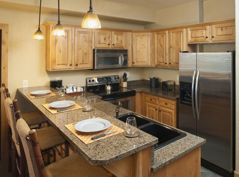 The fully-equipped kitchen features granite countertops and a breakfast bar