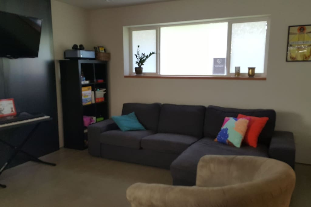 Comfortable living space looking onto additional seating area and kitchen. The flat screen TV is on an adjuatable mount so you can watch from any of the main living areas with ease.