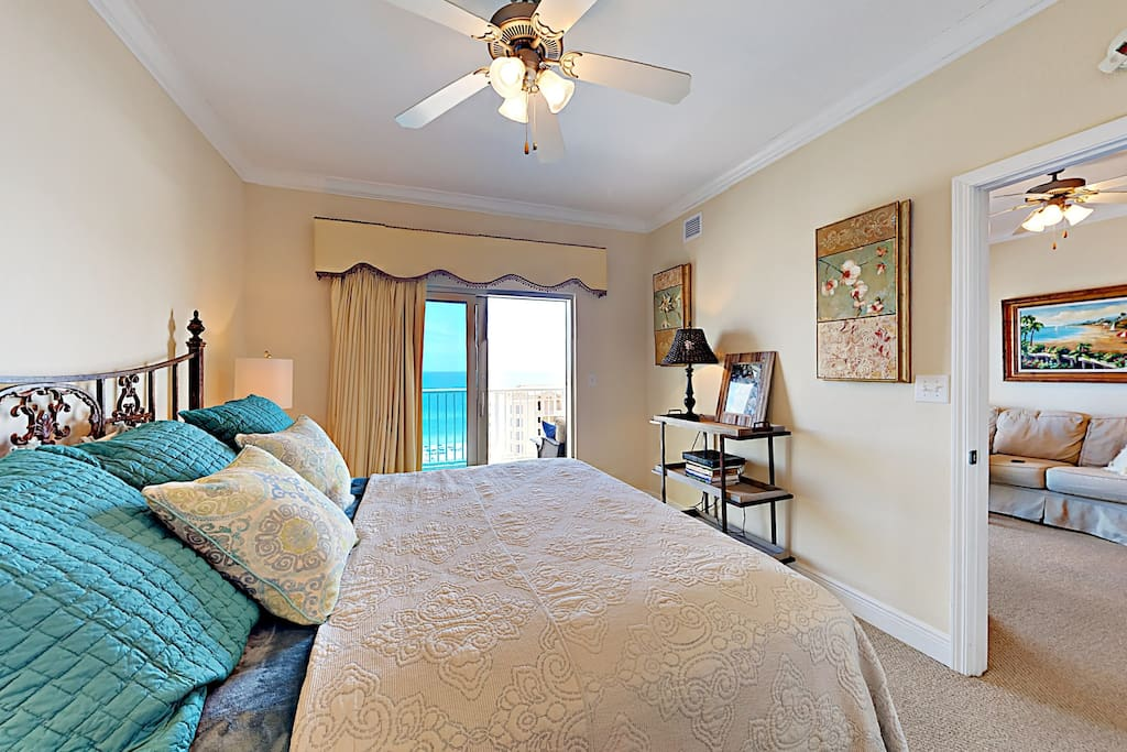 The master bedroom has a king-size bed and a sliding glass door to the balcony