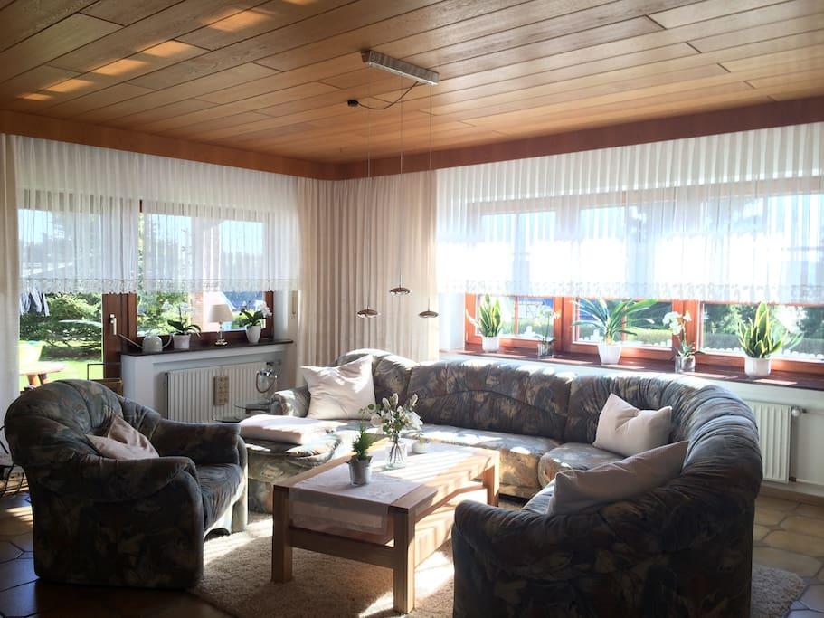Das lichtdurchflutete Wohnzimmer ist mit 2 modernen LCD-TVs ausgestattet