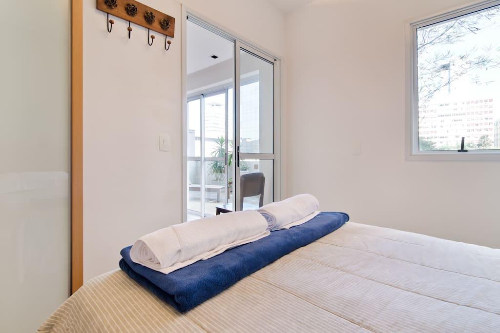Suíte bem iluminada com armário amplo, cabideiros e cortina para vedação
