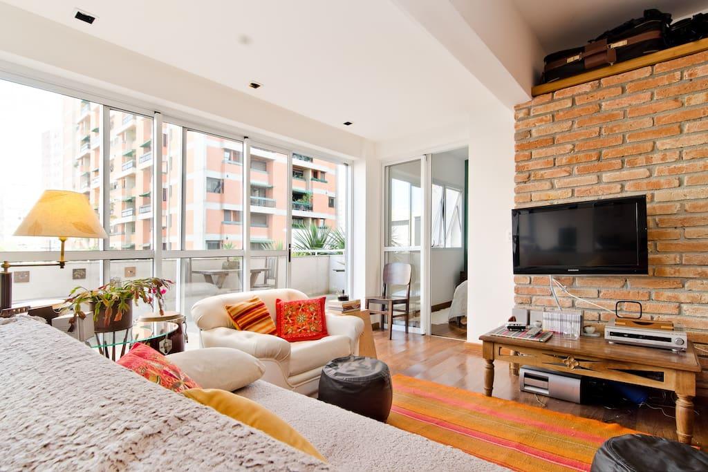 sala de estar com TV e DVD, e portas amplas de vidro de correr com acesso para varanda