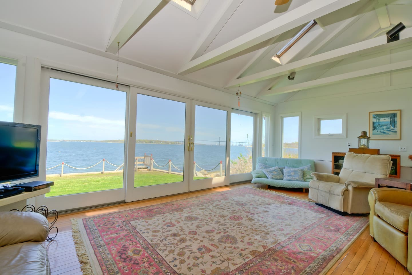 Living room with large sliding glass doors that open onto backyard and bay