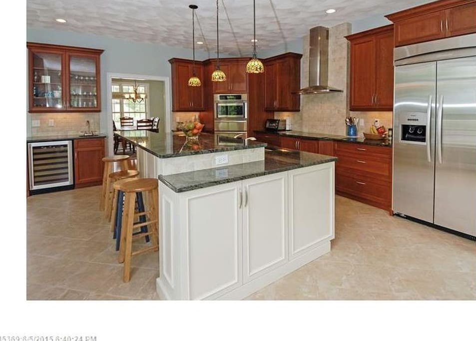 Huge island in kitchen with large fridge and wine fridge, granite counter tops, warming over, cook top, microwave, dishwasher, garbage disposal