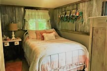 Romantic and Rustic, Beautiful ground floor Main Bedroom.  We feature quality linens, and locally sourced antiques.  The cabin is new construction, decorated to look rustic. Open the window, let the fresh air in and snooze or read a book.