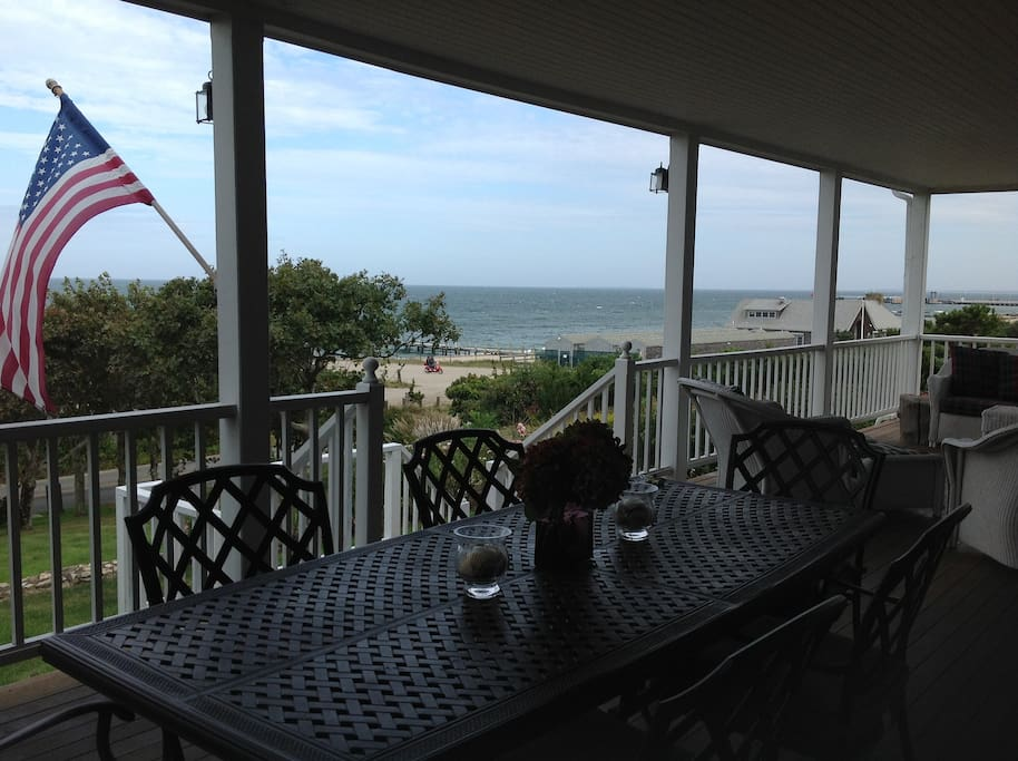 A large porch with a table for 8and large sofas and chairs to enjoy views of  Nantucket Sound