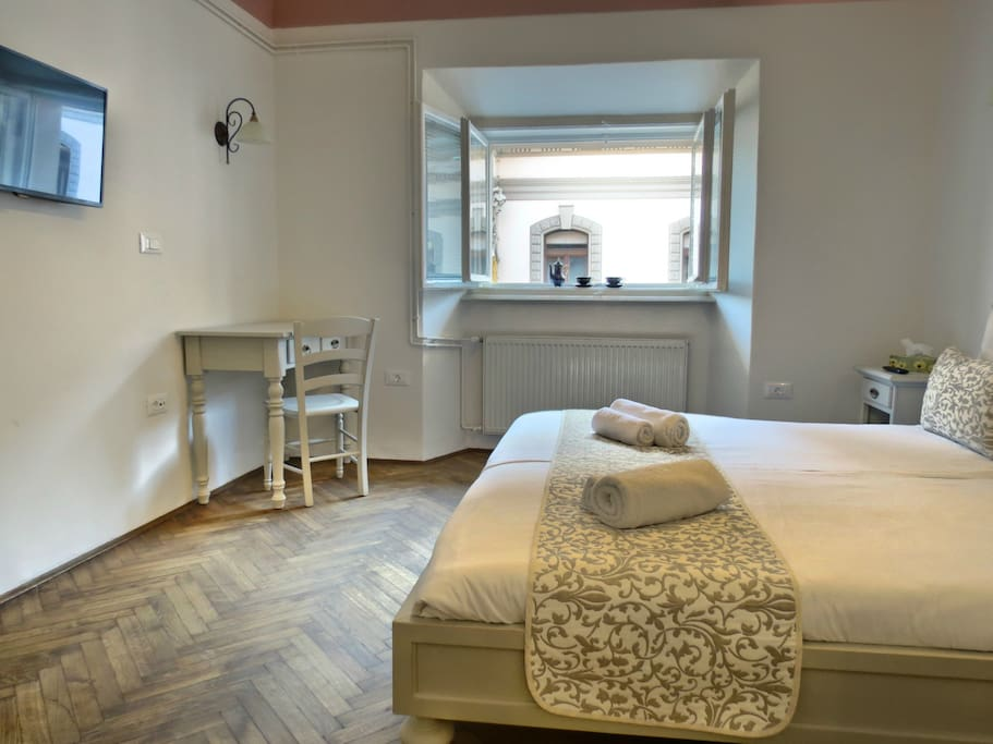Beautiful bedroom with a wooden flooring and the view on University building
