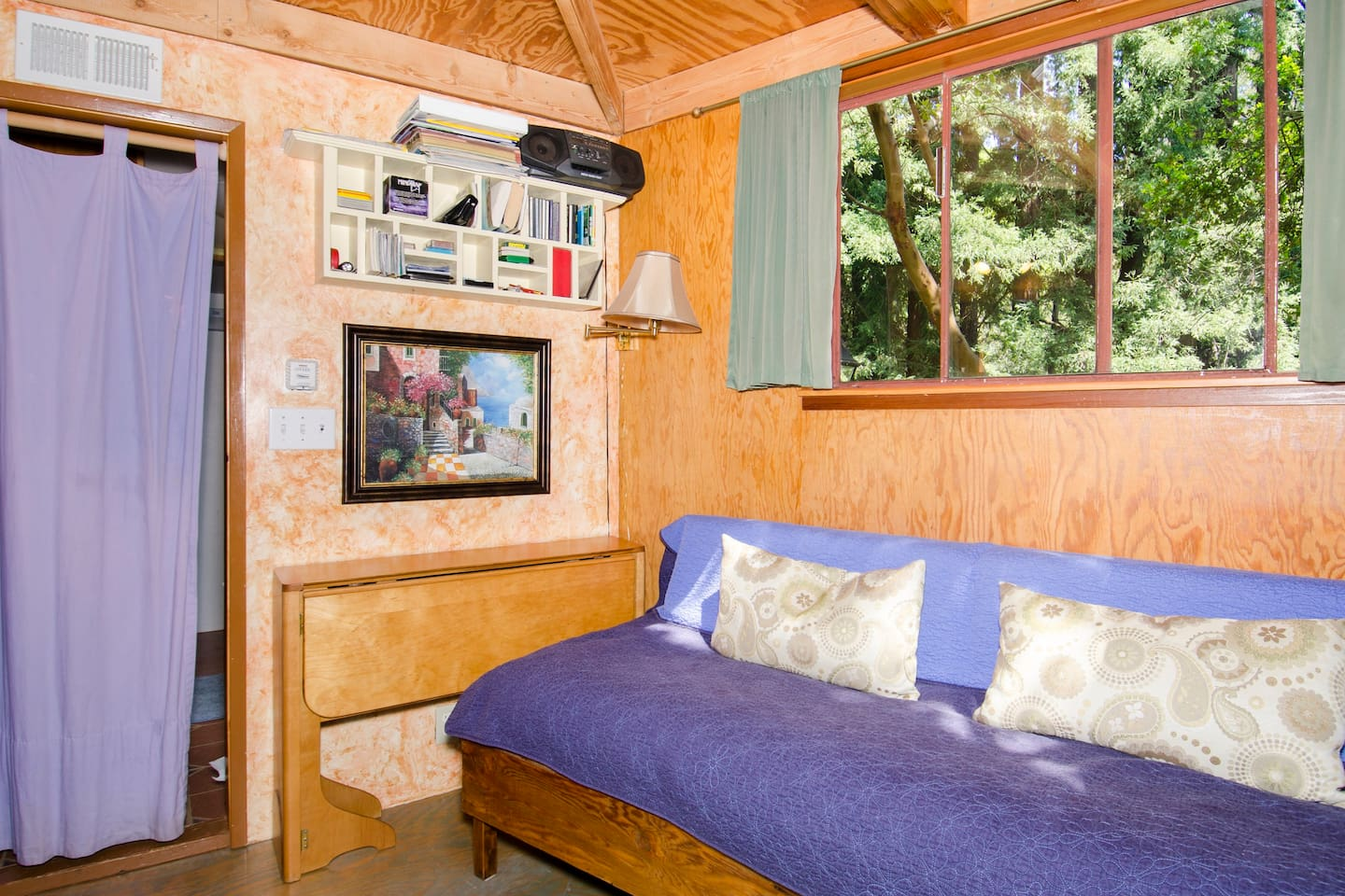 Downstairs is the couch, which can be used as the single bed. Up against the wall is the folding table. You can see the Redwood Grove through the window.