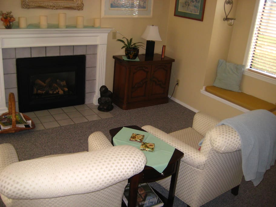 Fireplace with remote control and two comfy chairs.