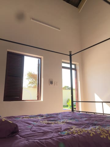 Master Bedroom looking outside the shuddered window onto pool, patio and garden