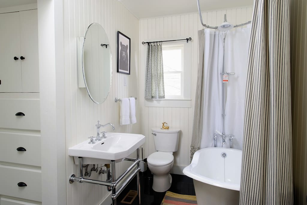 There is a claw-foot soaking tub with a shower in the bright, airy bathroom.