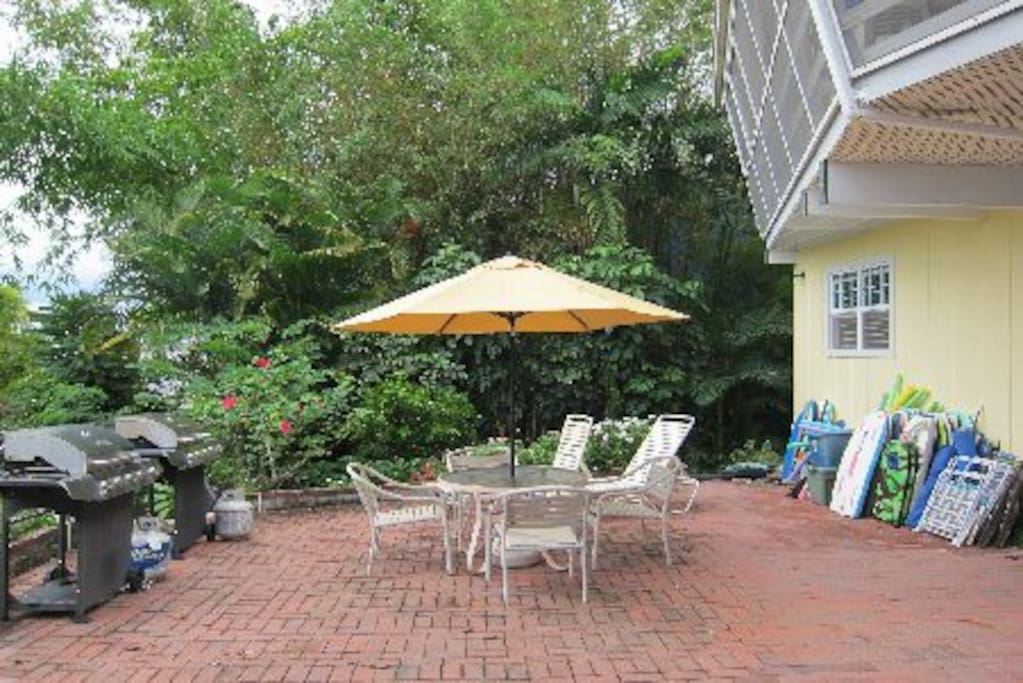The home  is  a  full two  stories  from both  sides  and this rear. Note the boogie boards, beach chairs & swim noodles on the wall.  This patio area may be  shared by others in the  house