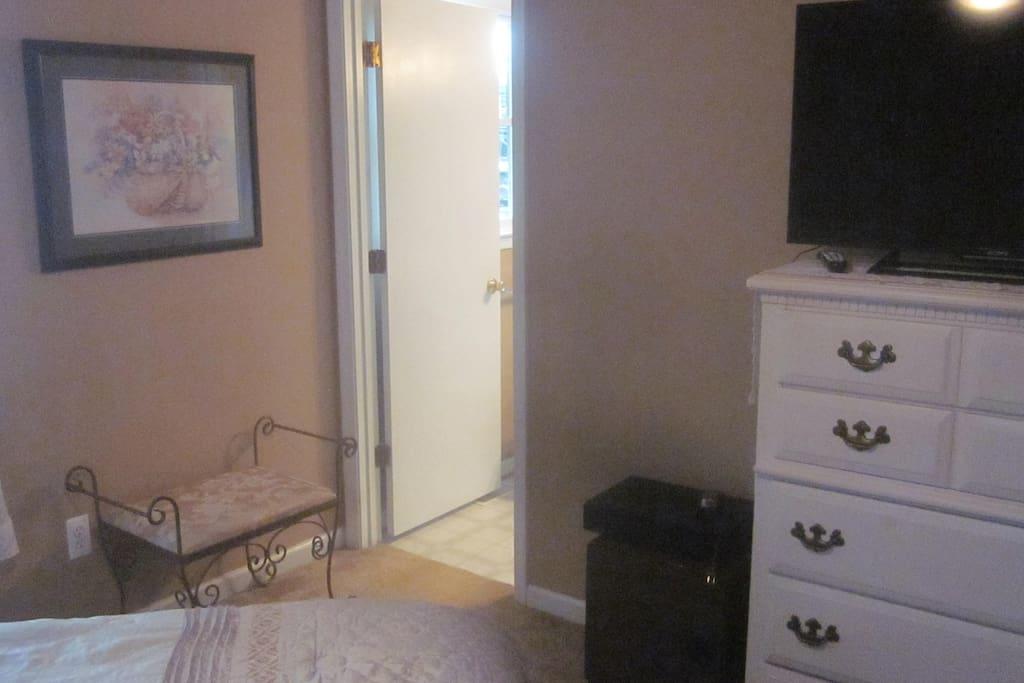 dresser, flat sceen tv for streaming movies, door to full bath,