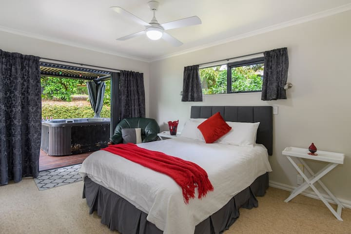"""Bedroom 1 Master with En-suite  French doors to deck with lovered gazebo, spa and garden.  The master bedroom is eqippped with a Fan.  """"David has a gorgeous home. His garden is beautiful and expansive, with many citrus and fruit trees dotted about the space. The yard space was large enough for the kids to play outside. The bedrooms and bathrooms were comfortable and spacious. The kids loved the bunk beds too. Kitchen was modern with all the amenities. There is also a hot tub which was a fun early evening activity. We also enjoyed the visits from his cat and dog! Highly recommended. We will stay here again if ever we are back in Tauranga.""""- Shwetha Dec 2020"""