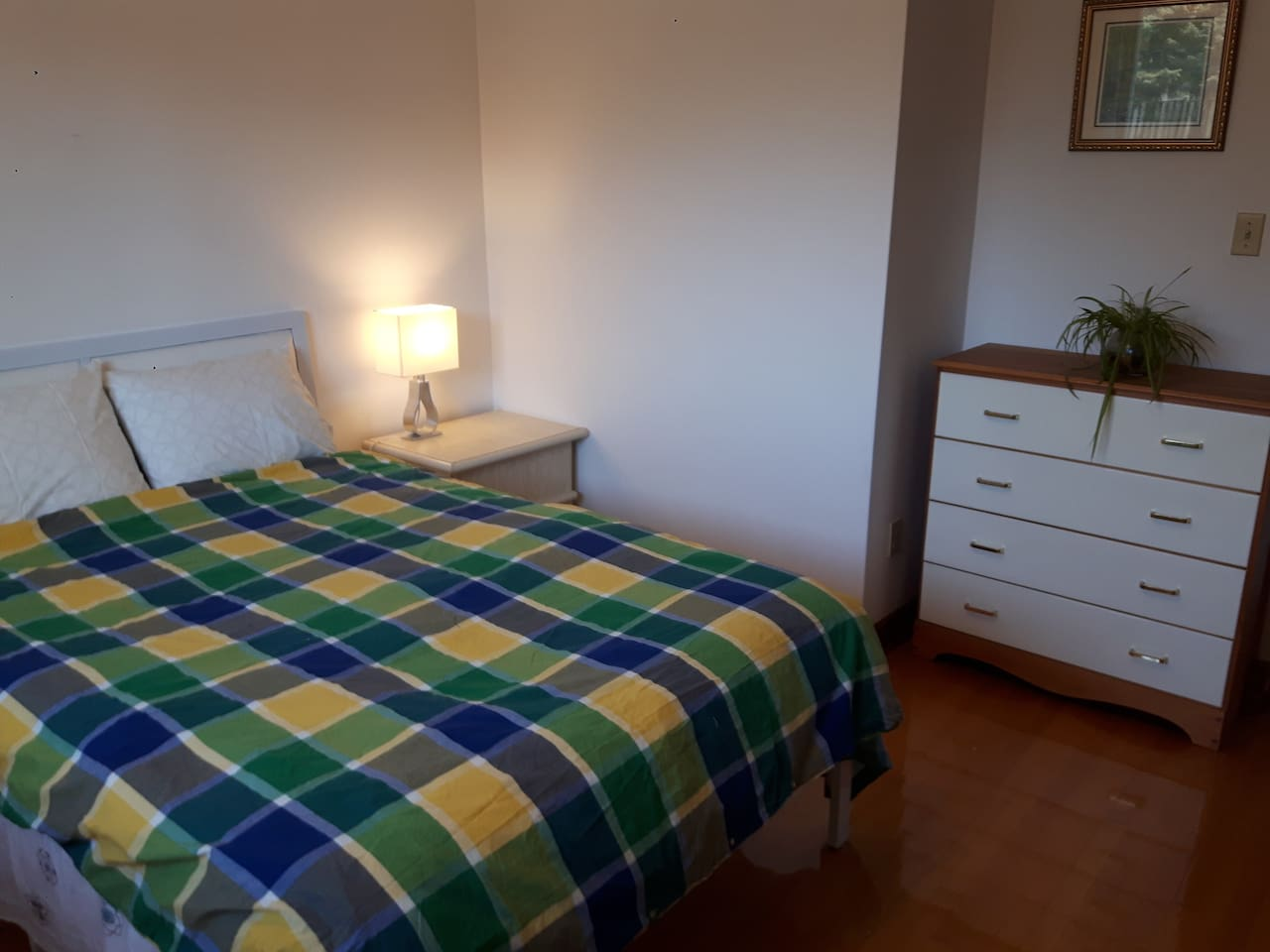 Spacious private room with a double bed, a nightstand, a lamp and a dresser