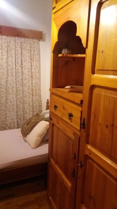 Bedroom with single bed, wardrobe and drawers. Everything is traditionally  handmade by the owner of the house who is a carpenter.