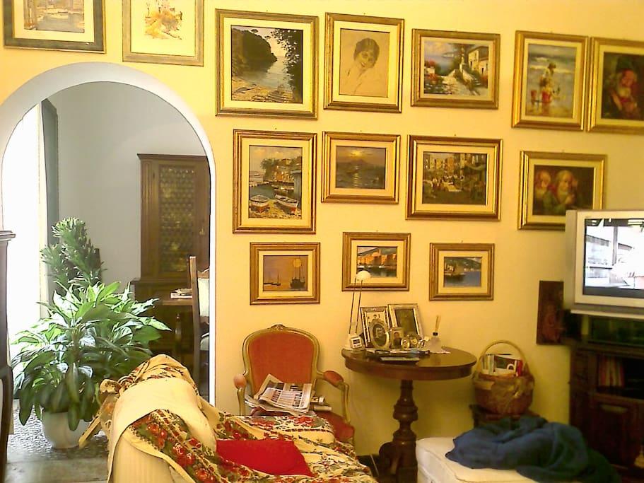 Salotto: parete con quadri e televisore. In fondo a sinistra la camera da pranzo.