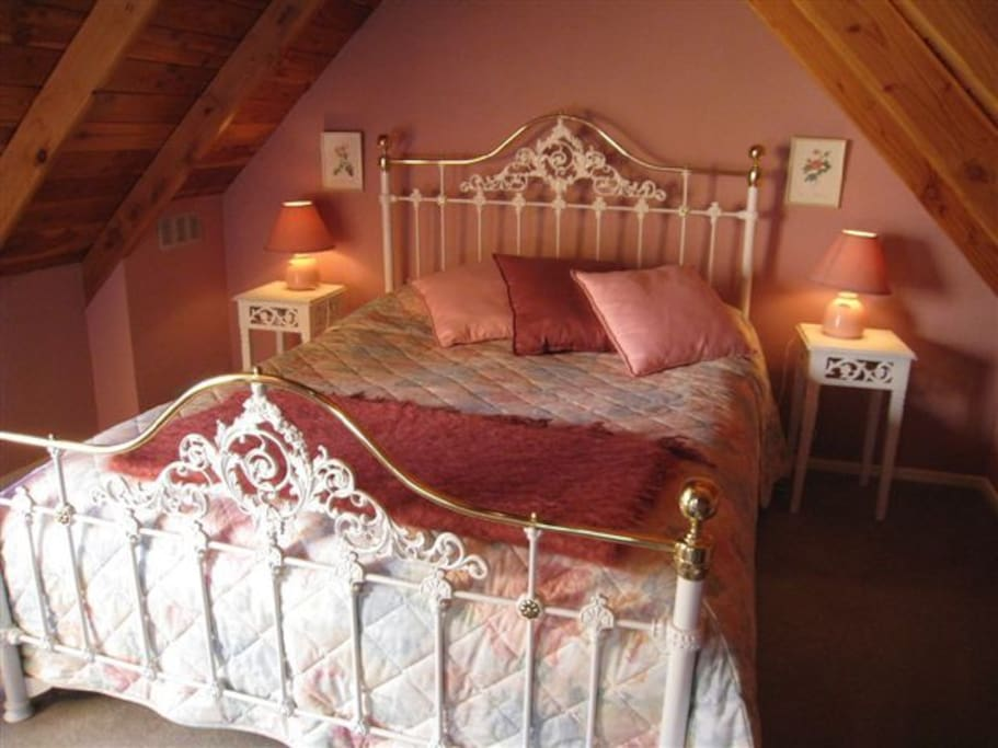 Queen bed up stairs with room for a cot or a rollaway bed. Balcony opens out to garden and river views.