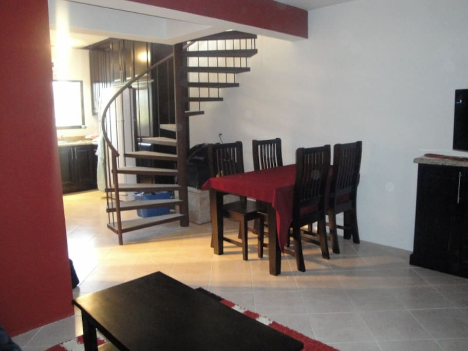 Dining area, spiral staircase and kitchen.
