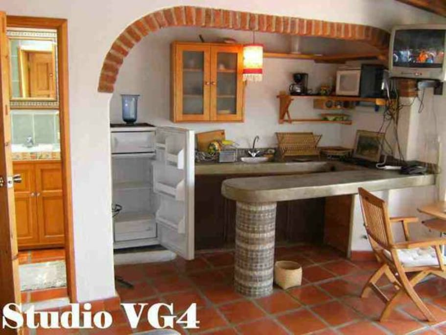Galley-style kitchen with stove, microwave, fridge