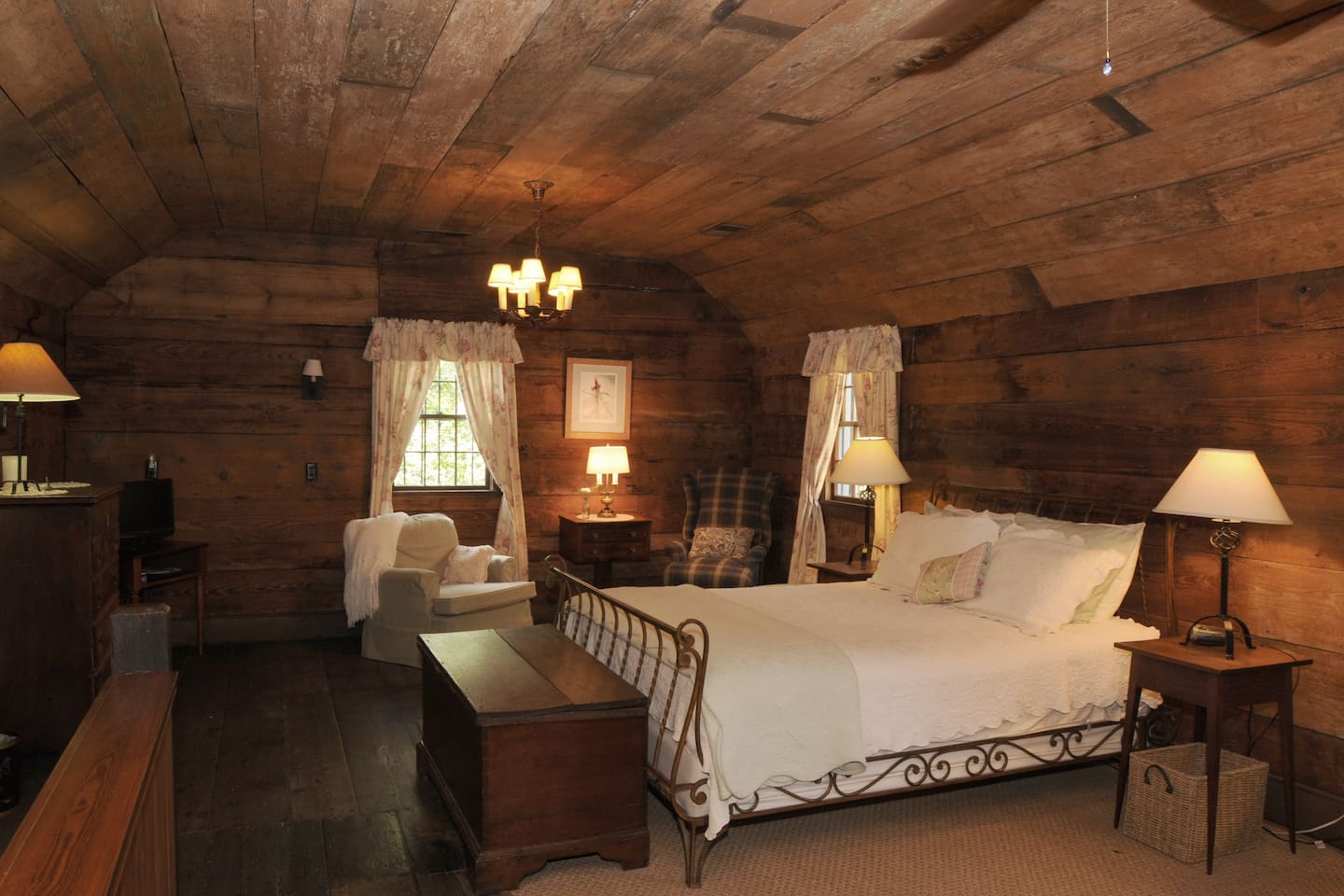 Original heart pine floors, walls and ceiling surround Queen bed and seating area upstairs.