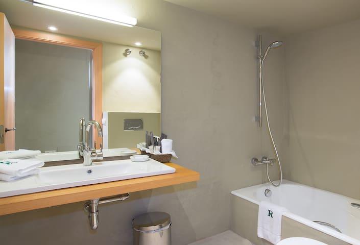 Baño con bañera y ducha. equipado con toallas y secador de pelo.