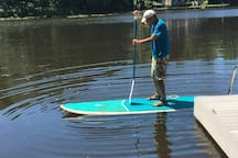 One of our guests trying out the  stand up paddle board mid June 2018.  Note swimming pool stairs to the lake.   Yucky to wade in unless you are a dog.  Lake is six feet deep where paddler is.