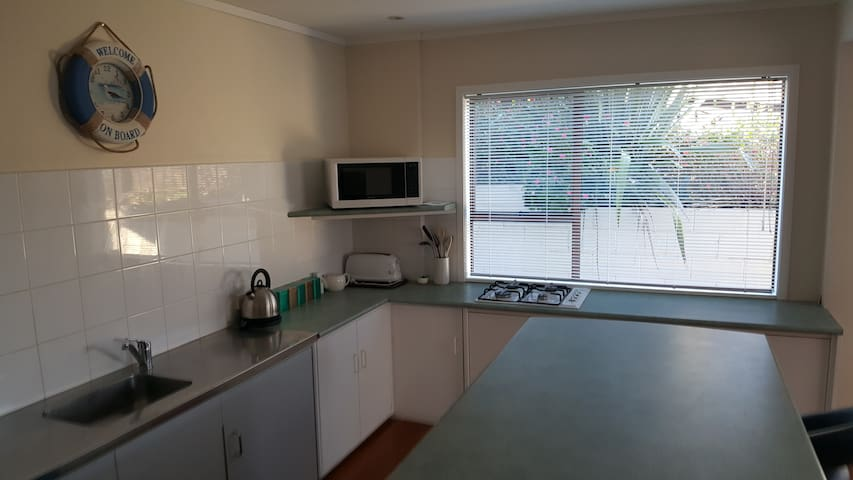 Nice bright kitchen with stove, hob, microwave, fridge, and plenty of cutlery and crockery. The bench is the right height for disabled folk in wheelchairs.