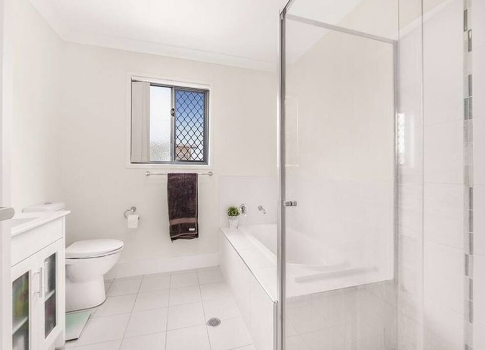 The guest bathroom is large and fitted with both bath and shower.