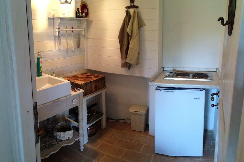 Kleine Küche mit Eisschrank, Herd und Küchenutensilien im Rosenzimmer