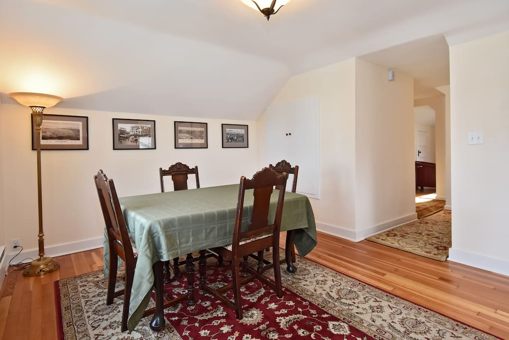 Formal dining room with seating for 4. Antique furnishings and historic photographs of Seattle at the turn of the century