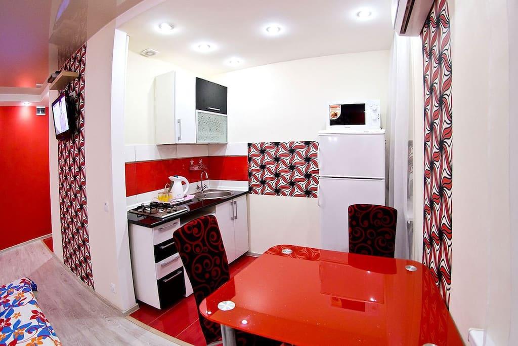 На кухне газовая плита, СВЧ, холодильник, электрочайник, посуда.