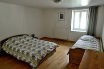 La Chambre triple avec un grand lit et un lit simple.