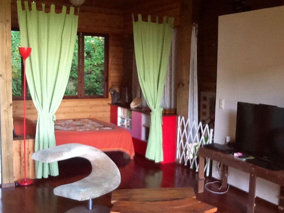 Partie chambre de l'espace privé loué, fermé par des rideaux du reste de la maison
