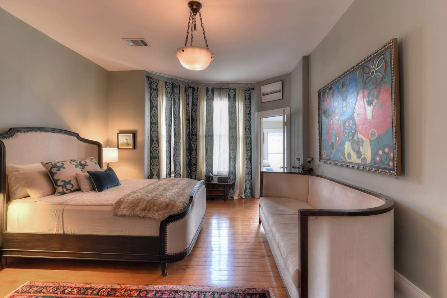 Queen bed and twin-sized sofa.  French door leads to ante-room with chaise lounge, table and four chairs, and private door to veranda.