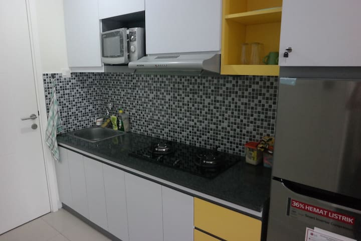 Your small kitchen, with microwave, gas stove, cooking and dining utensil