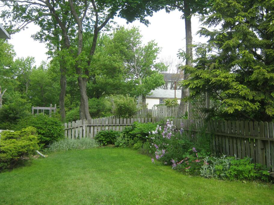 Fenced backyard with mature perennial garden, brick steps to lower-level pathway. Two level deck, with both sunny and shady areas, Weber gas bbq and patio dining set and Adirondack chairs.
