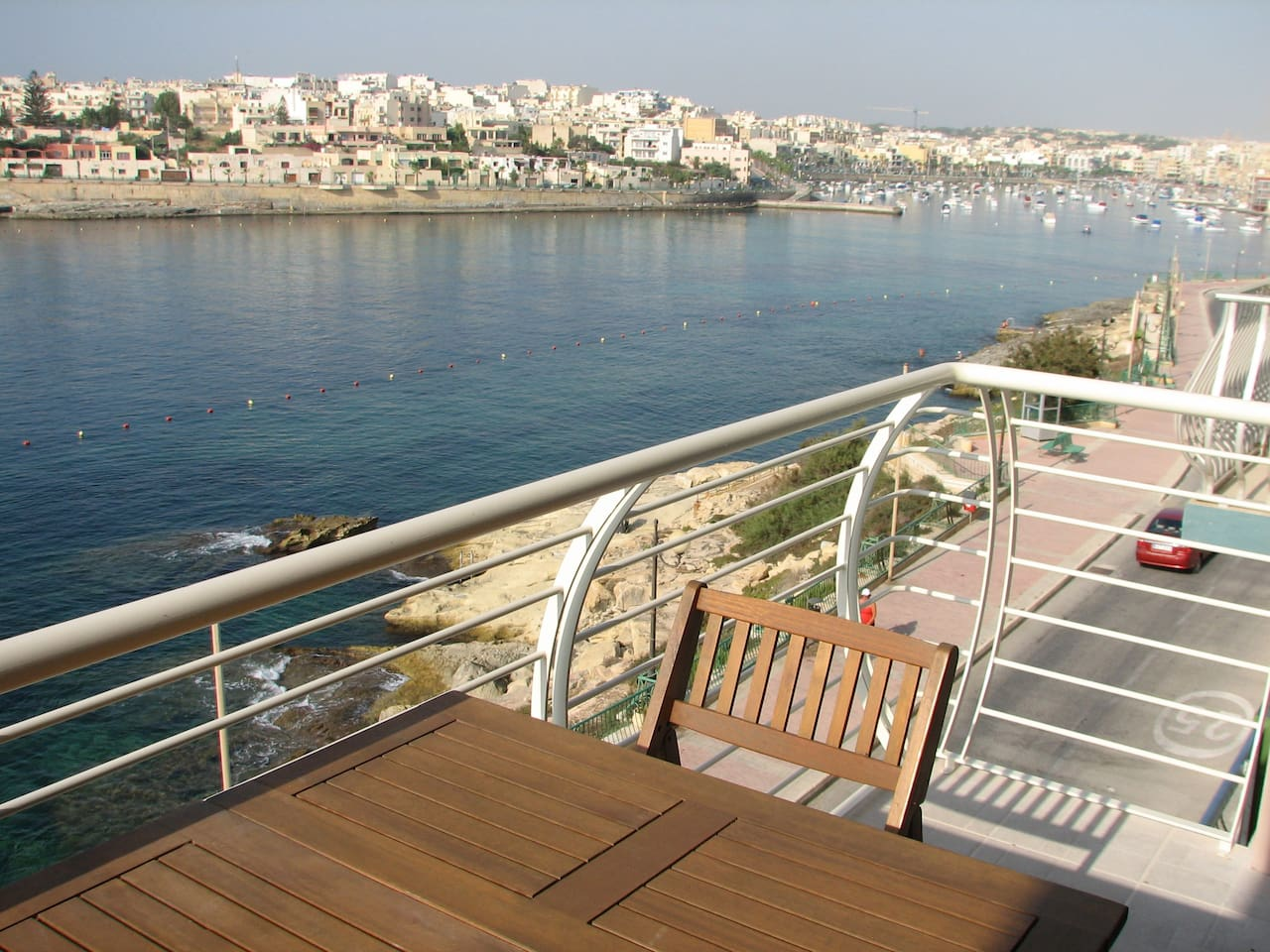 View From Balcony, Balcony consists of an outdoor table and 4 chairs. Swimmers zone is indicated by buoys floating .
