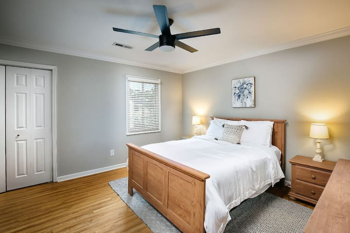 King sized bed, large closet, dresser with mirror, 2 nightstands and desk area.