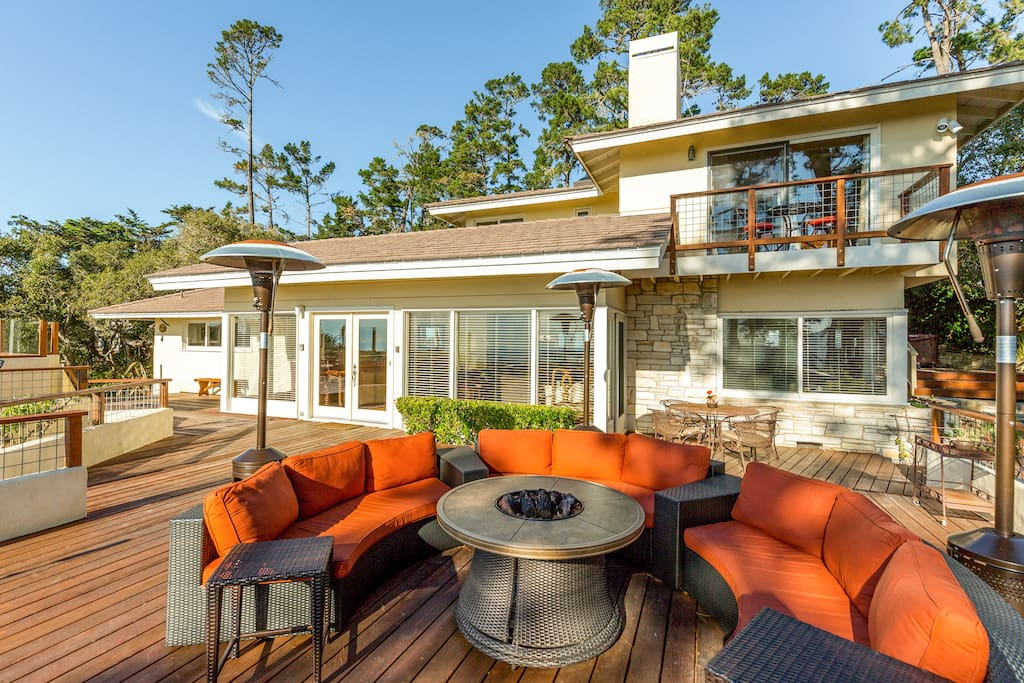 On the spacious deck, cushioned furniture offers comfy seating around a gas-powered fire pit.