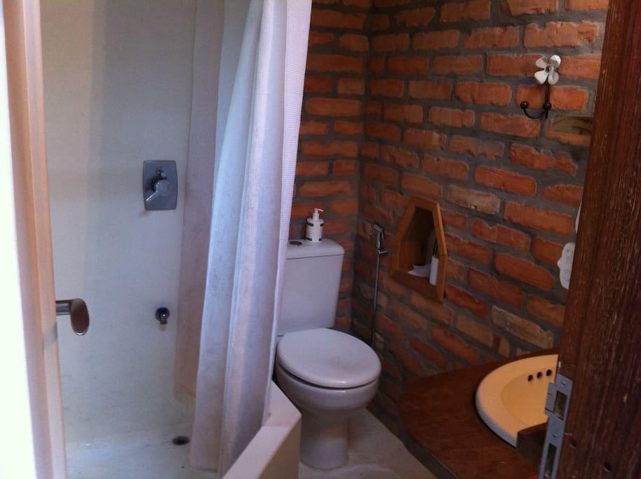 banheiro com chuveiro e banheira pequena