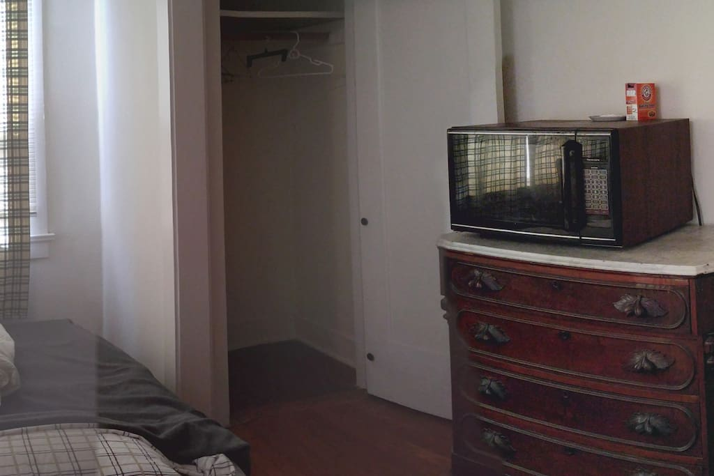 Rightside of one spacious 12x18 Room, Twin Bed, Closet, Antique Dresser, Refrigerator.
