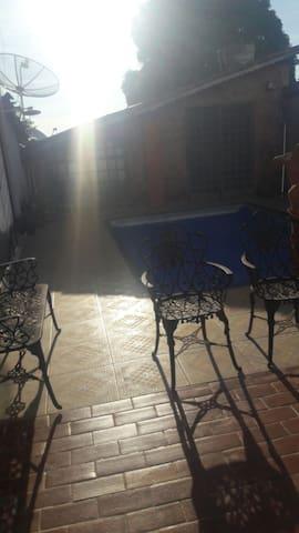 Área de lazer c uma picina q mede cinco metros por três, com ducha e algumas plantas.