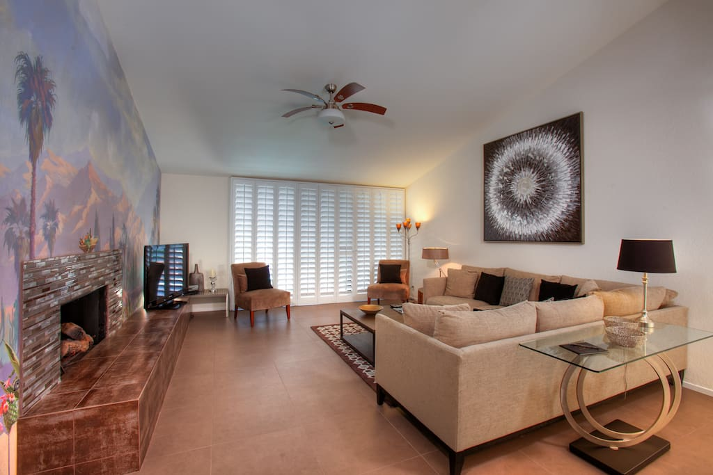 """Gather with family and friends in this comfortable living area with huge sectional, two side chairs, fireplace, sparkling wet bar, 55"""" Flat Screen with Blu-Ray and stunning wall mural commission by renowned British muralist, Michael Alford, inspired by the dramatic view of Mt. San Jacinto."""