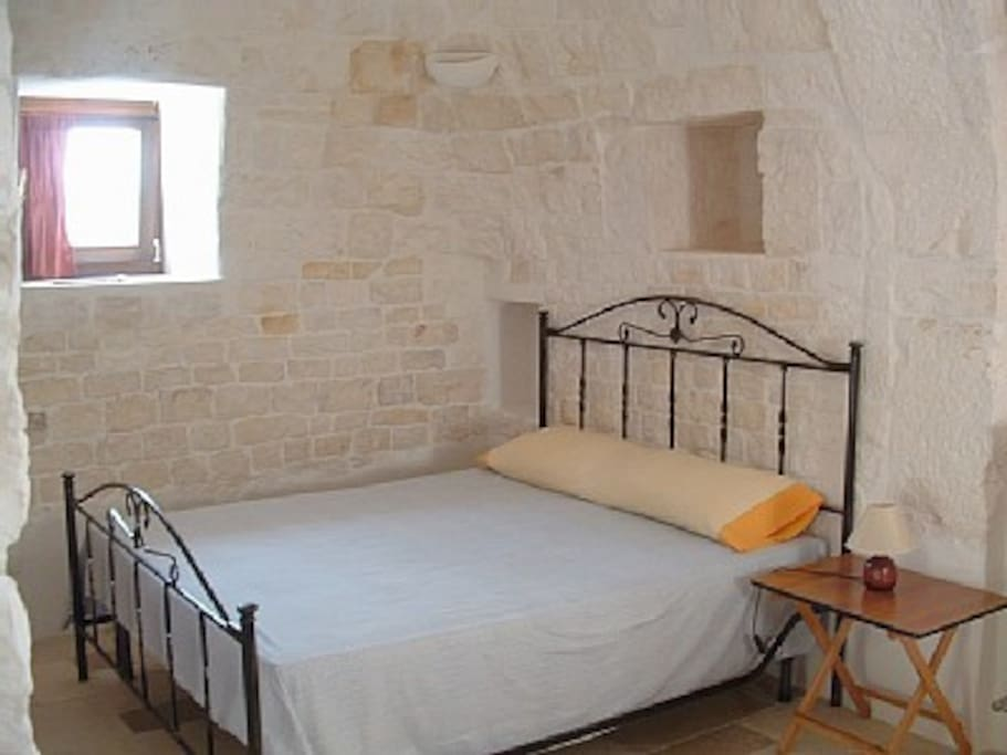 The bedroom underneath the cone of the trullo.