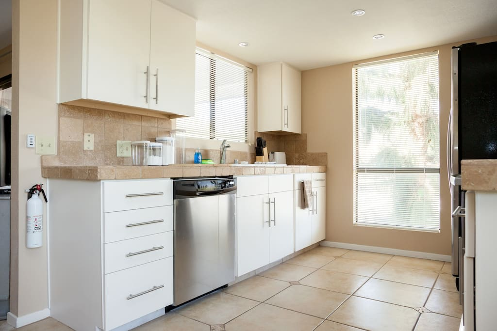 Kitchen with full-size dishwasher and sink overlooking patio.