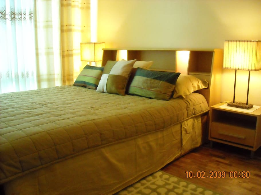 Lighted headboard queen size bed next to floor to ceiling, wall to wall windows